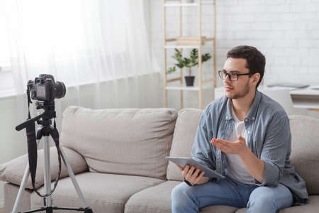 Social media at home. Young creative smart man sitting on sofa, makes video for blog at home in daylight in interior Stockfoto