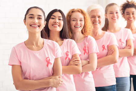 Breast Cancer. Multicultural Ladies In Pink T-Shirts With Oncology Awareness Ribbons Standing In Line Over White Background. Selective Focus Standard-Bild
