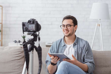 Video blogger at workplace at home. Smiling young man in glasses with tablet in hands speaks to camera in light living room interior Stockfoto