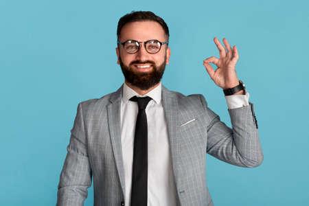 Happy businessman in formal suit showing okay gesture on blue studio background
