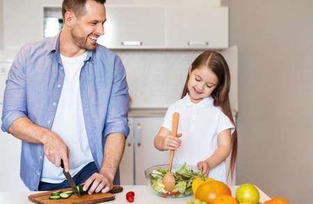 Family Cooking Food Concept. Happy Father And Daughter Making Fresh Veggie Salad In Kitchen At Home.
