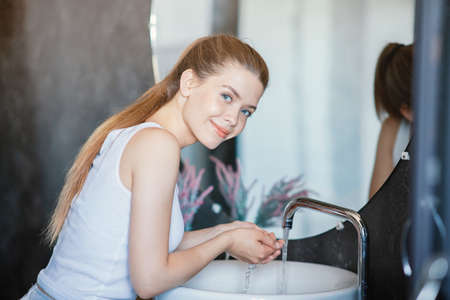 Daily hygiene. Pretty young lady washing her face in front of mirror at bathroom
