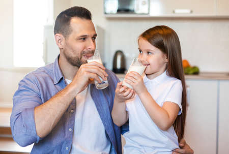 Breakfast With Dad. Father And Little Daughter Drinking Milk Sitting In Kitchen At Home Stock fotó