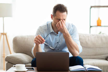 Fatigue From Work. Tired man feeling eyestrain, holding glasses, rubbing dry irritated eyes, massaging nosebridge Stock Photo