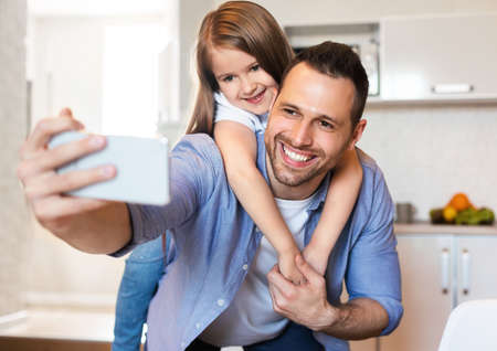 Cheerful Dad And Daughter Making Selfie On Smartphone Having Fun In Kitchen At Home. Weekend With Father. Selective Focus Stock fotó