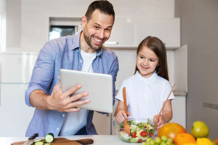 Happy Father And Daughter Using Tablet Computer Cooking Together In Kitchen At Home On Weekend. Online Family Cooking School Concept