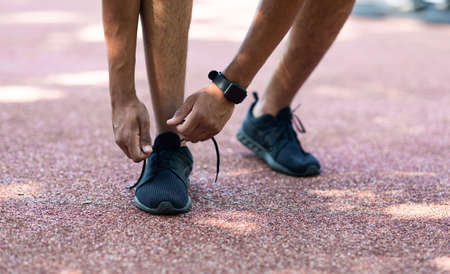 Millennial sportsman tying laces of his shoes on jogging track, close up of legs