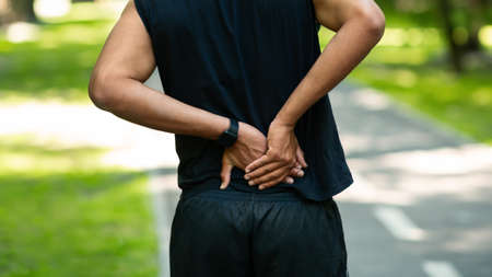 Young black sportsman suffering from pain in his back during workout at park, close up. Panorama