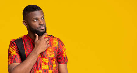 Thoughtful man in african traditional clothes looking at empty space, yellow background, panorama