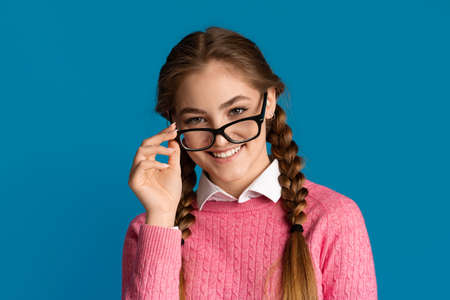 Good mood at school. Smiling teenage girl takes off glasses, close up isolated on blue background, studio shot Banco de Imagens