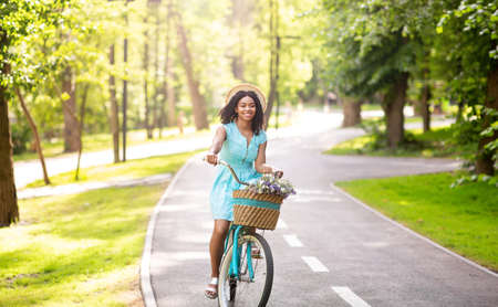 Cheerful black woman riding bicycle at park on sunny day, panorama