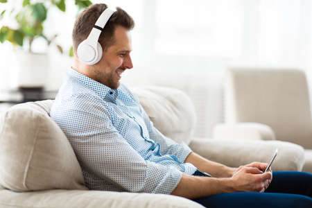 Enjoy The Music. Happy adult man listening to his playlist on mobile phone with headphones. Free space, side view
