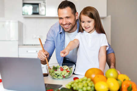Online Recipes. Cute Father And Daughter Cooking Using Laptop Preparing Dinner Together In Kitchen At Home. 版權商用圖片