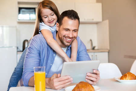 Joyful Father And Daughter Using Digital Tablet During Breakfast In Kitchen At Home. Weekend Morning Concept