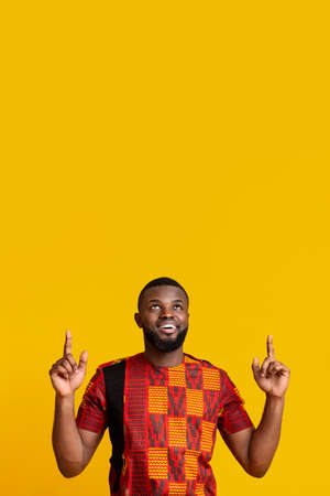 Handsome african american man in traditional clothes pointing up at free space over yellow background 写真素材