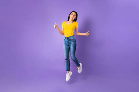 Funny portrait on joyful young woman jumping with thumbs up isolated on pastel purple studio background, full length
