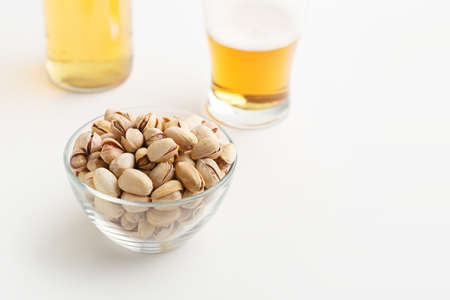 Beer traditions and appetizer. Pistachios with peel in glass plate, nearby are unfinished glass of light ale and bottle with drink, close up, free space