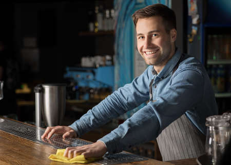 Friendly client meeting. Smiling handsome man in apron, wipes bar counter in interior of modern pub