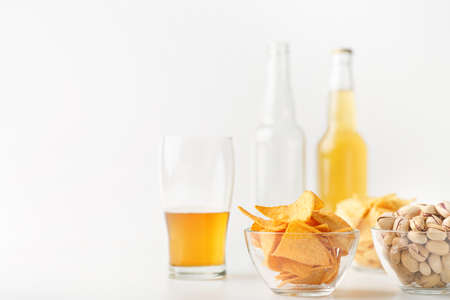 Set of snacks and beer for clients. Half glass of beer, empty and full bottle, nachos, chips and pistachios in glass plates on white background 免版税图像