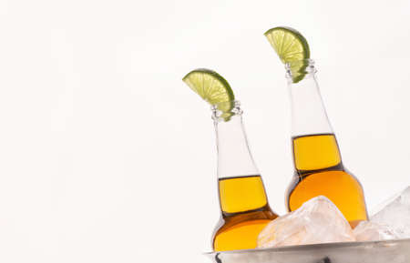 Cold drink. Transparent beer bottles with light ale and slice of lime in metal bucket with ice isolated on white background 免版税图像
