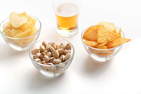Appetizer in bar. Pistachio, chips and nachos in glass plates and glass of light beer on white background, free space 免版税图像