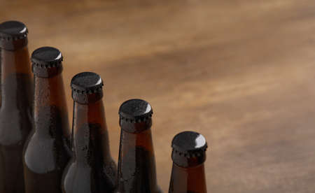 Beer industry. Row of dark beer bottles with caps on brown wooden background, close up