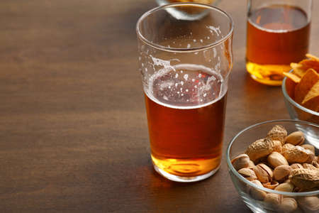 Client drink. Unfinished glass of beer and bottle, pistachio, chips in glass dishes on wooden table, close up, free space 免版税图像