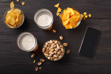 Food in pub for beer. Smartphone on dark wooden table, nearby are nachos, chips and pistachios in glass plates and two glasses of beer, top view, free space