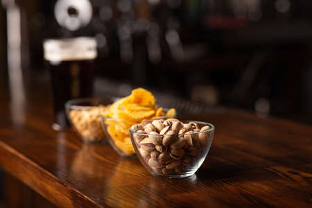 Snack to beer. Pistachios, chips and peanut in glass bowls on wooden brown bar counter, free space