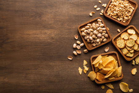 Delicious food to beer. Crackers, peanuts, pistachios and chips in square plates on brown wooden table in pub, top view, close up, free space