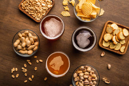 Client service in pub. Dark, light, unfiltered beer in glasses, nuts and chips in plates on wooden table, top view, close up