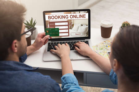 Back view of couple making hotel reservation online, using laptop and credit card, hotel booking website concept Foto de archivo