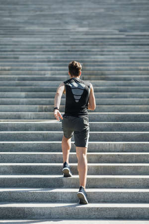 Running up stairs. Young man in sportswear and with fitness tracker on hand, goes in for sport in city, free space