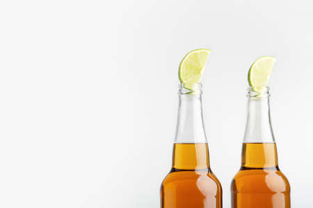 Beer with lemon. Bright lager in bottles isolated on white background, side view, free space
