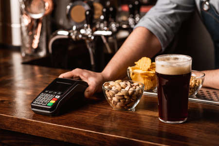 Payment for beer set. Bartender gives contactless terminal, near pistachios, chips and nuts in plates, and dark beer with foam in interior of pub Reklamní fotografie