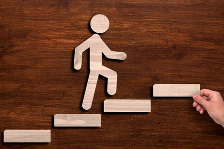 Career Growth Concept. Hand Putting Steps For Stickman Over Brown Wooden Background. Collage