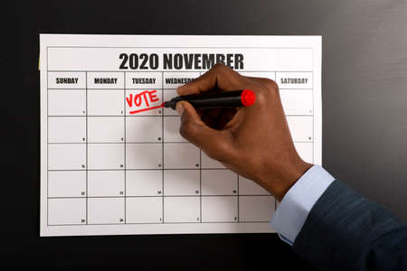 African american businessman writing Vote on November 3, 2020, presidential elections, patriotic concept
