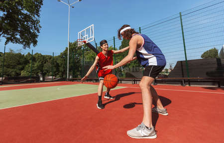 Two sportsmen playing game of basketball at outdoor court, empty space. Panorama
