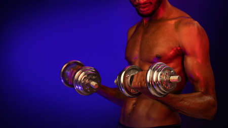 Strength Workout. Unrecognizable Athlete Guy Exercising With Dumbbells Standing Shirtless On Blue Background. Studio Shot