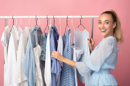 Portrait of cheerful girl choosing clothes standing near rack with hangers, looking at camera