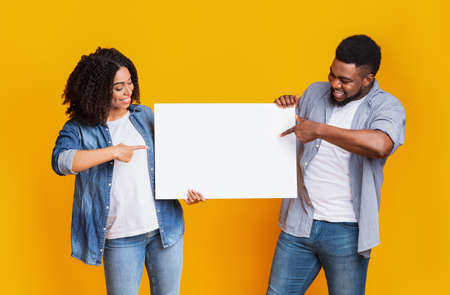 Cheerful black couple holding and pointing at blank advertising board with copy space for text, standing on yellow background Imagens