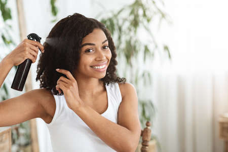 Hairstyling. Smiling Black Woman Applying Texturising Spray To Her Beautiful Curly Hair At Home, Getting Ready To Go Out, Copy Space