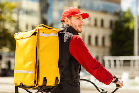 Food Delivery Concept. Courier With Yellow Backpack Delivering Food On Bicycle Riding In Urban Area Outside.