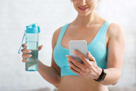 Good news in smartphone. Muscular woman in sport bra with bottle of water looks at phone and smiles, on light background, copy space Banco de Imagens