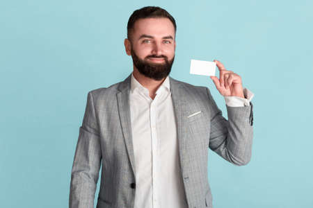 Happy CEO showing business card with empty space for design against blue background