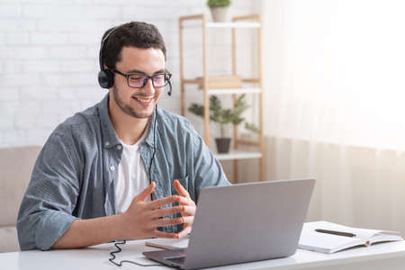 Conversation with client and video call. Smiling guy with glasses and headset gesticulating with hands and watching laptop in interior of living room Banco de Imagens