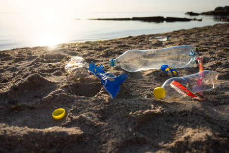 Beach Pollution Concept. Plastic Litter Trash Lying On Sand Near Sea Polluting Seashore. Ecological Background