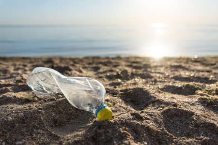 Sea And Ocean Pollution. Plastic Bottle Trash Lying On Sand Beach Near Water, Ecology Background. Copy Space