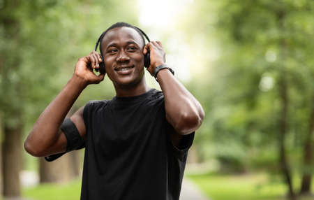 Music for exercising. Joyful black jogger putting wireless headset on his head, training at park, looking at free space