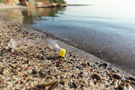 Beach Pollution Concept. Wasted Plastic Bottle Litter Lying On Sand On Sea Shore Near Water. Blank Space For Text